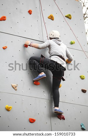 the image of Girl exercises on indoor rock climber - stock photo