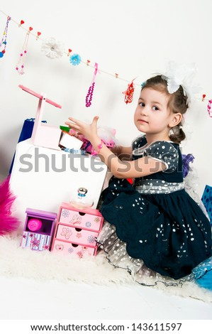 The image of the elegant girl playing with cosmetics and jewelry - stock photo