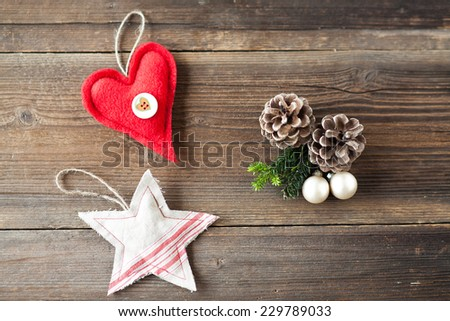 The image shows a composition on wooden background of a red heart and a star of fabrics and other decorative elements christmas as pineapples and tree balls and fir branches - stock photo