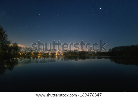 The image shows a landscape and a starry sky. - stock photo