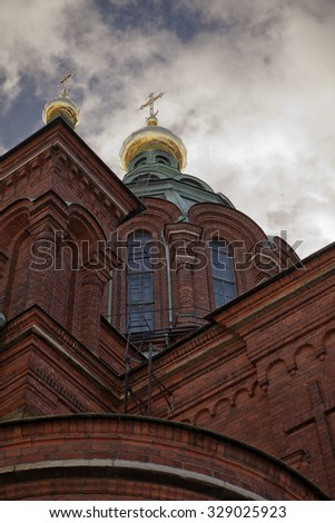 The imposing brick facade, central dome and golden cross of the Uspenski Cathedral, a Russian Orthodox church, in Helsinki, Finland. - stock photo