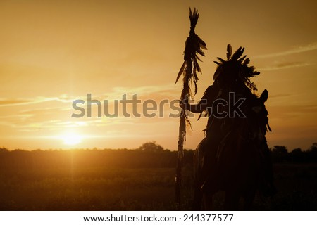 The Indians are riding a horse and spear ready to use In light of the Silhouette - stock photo