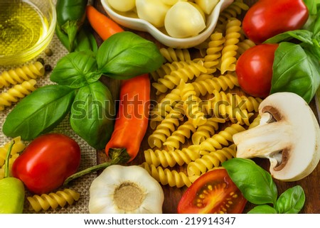 The ingredients of Italian cuisine, pasta, tomatoes, Basil, mushrooms, peppers, garlic, cheese, olive oil. - stock photo
