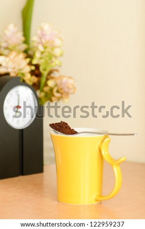 The instant coffee spoon on the coffee cup  yellow - stock photo