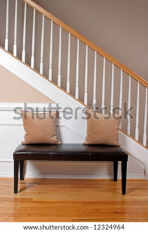 The interior entry of a home with a leather bench, stairway and hardwood floors. - stock photo