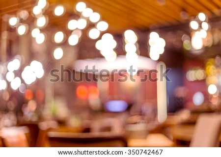 The interior of a small restaurant a blurred background. Blurred bokeh cafe interior in warm dark colors. As background for creative fashion design. - stock photo