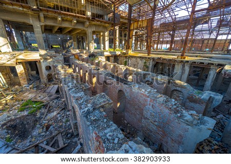 The interior of an abandoned old factory building. Impressive ruins of modern architecture. - stock photo
