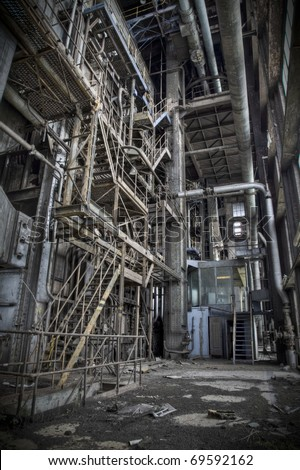 The interior of an old abandoned machine hall, with the control room in front and the staircase to reach the upper deck on the left. - stock photo