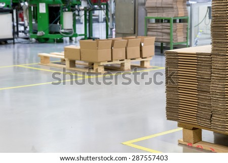 The interior of the assembly hall with a designated communication zone and cardboard stored on wooden pallets. All potential trademarks are removed. - stock photo