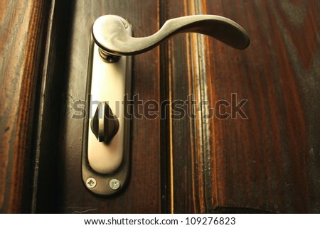 The iron doorhandle on the wooden doors close - stock photo