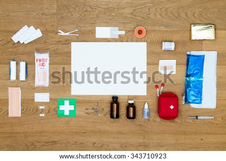 The items and objects in a first aid kit, neatly aligned on a wooden surface, with a blank card for a message or text as copy space available. Items include pliers, bandages, plaster, and much more. - stock photo