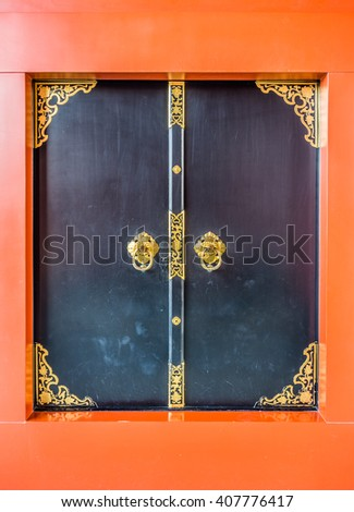 The Japanese art of black wooden doors with golden floral pattern and orange frame - stock photo