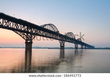 the jiujiang yangtze river bridge  in sunset , is a combined road and rail bridge . - stock photo