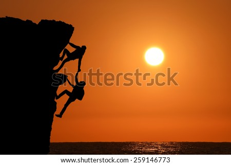 The joint work teamwork of two men travelers help each other on top of a mountain climbing team, a beautiful sunset sea ocean landscape - stock photo