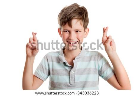 the joyful boy crossed fingers for good luck - stock photo