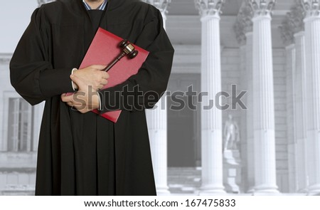 The judge hammer with a judge on the background of the courthouse - stock photo