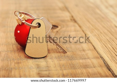 The key with Christmas ball on wooden background - stock photo