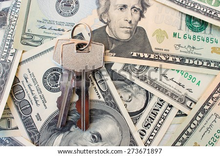 The keys on a background of money. The concept of buying or renting a home. - stock photo