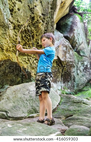 The kid shoots a bow in the park - stock photo