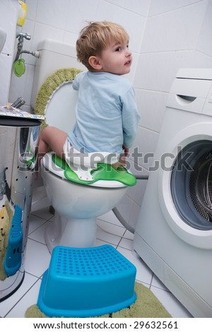 The kid sits on the toilet and laughs - stock photo