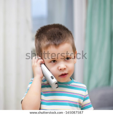 the kid speaks by phone at home - stock photo
