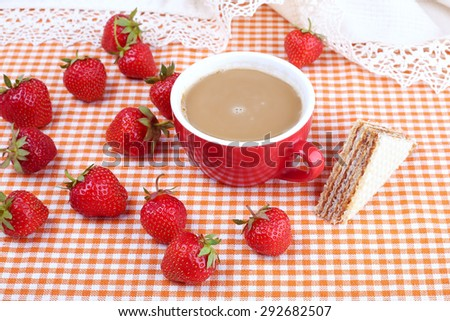 The kitchen table with a cup of coffee, dessert and strawberries. Strawberry berry, waffle cake and a cup of hot coffee with milk. Summer berries. Breakfast, snack, food.  - stock photo