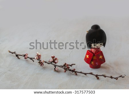 The kokeshi  doll in the Japanese kimono and a sprig of cherry blossoms. The concept of hanami either contemplation - stock photo