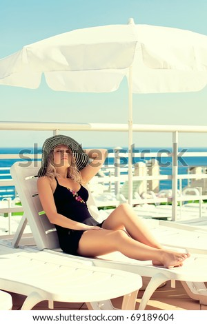 The lady in a hat sunbathes on the yacht in the sea - stock photo