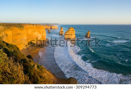 The landmark Twelve Apostles glowing yellow at sunset, along the famous Great Ocean Road in Victoria, Australia - stock photo