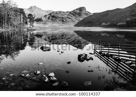 The Langdale Pikes reflected in Blea Tarn, Little Langdale, in the Lake District - stock photo