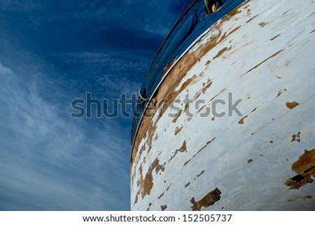 The large hull of a trawler in the process of being scraped sanded and painted - stock photo