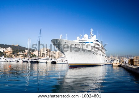 The large white private yacht alongside the dock. - stock photo