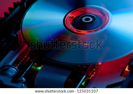The laser disk lies in the open disk drive. Parts of electronic schemes are visible - stock photo