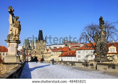 The late Snow in March Prague - gothic Castle above the River Vltava with the Charles Bridge - stock photo