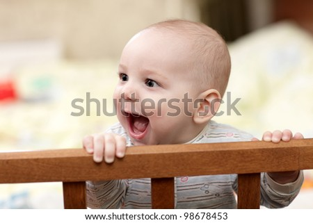 The laughing baby in a cot at home - stock photo