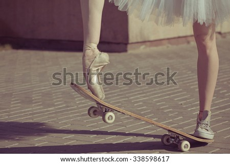 The legs of a ballerina on a skateboard. Feet shod in sneakers and ballet shoes. Modern fashion. Photo closeup. - stock photo