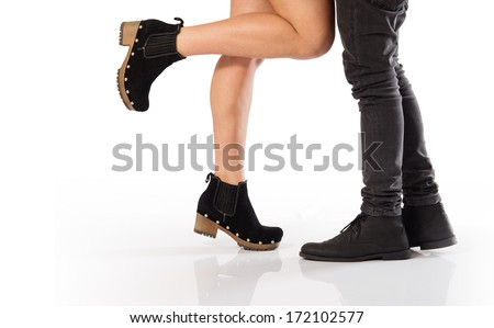 The legs of a couple of sweethearts facing each other isolated in white - stock photo