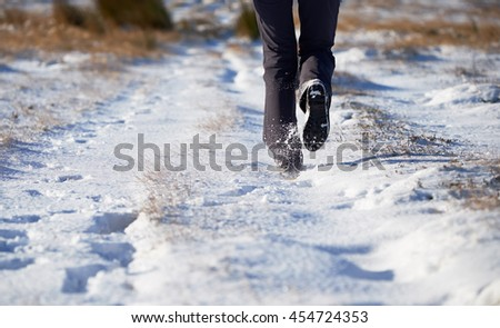 The legs of a hiker and their dog walking through a snow covered winter landscape. Edmondbyer Common, England, UK. - stock photo