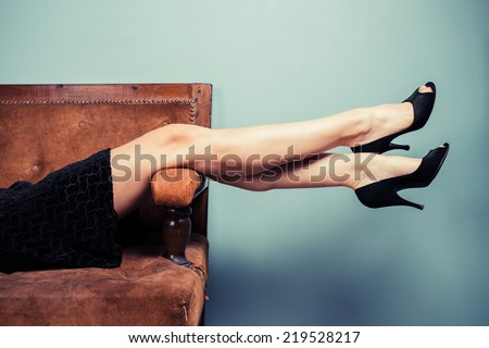 The legs of a sexy young woman lying on a sofa - stock photo