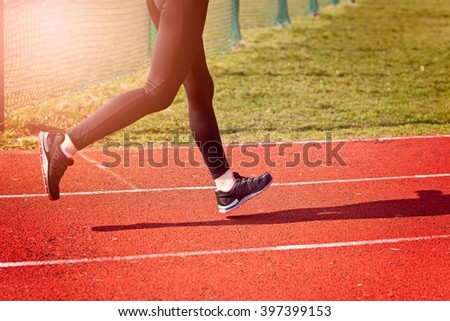 The legs of a woman running around the track on a sunny spring day. Woman running concept.  Runner jogging training workout  - stock photo