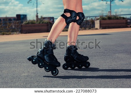 The legs of a young woman as she is rollerblading on a sunny day - stock photo