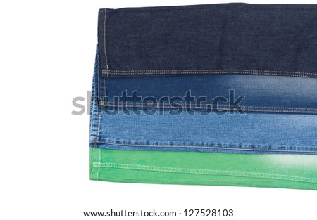 The legs of four different pairs of jeans overlaid to display the different colours of denim fabric from green through blue to navy blue isolated on white - stock photo