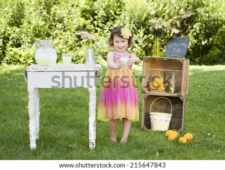 The Lemonade Stand.  Adorable little girl trying to sell lemonade at a roadside stand.   - stock photo