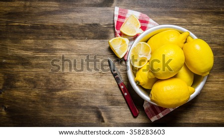 The lemons in the cup with a knife on the fabric.  On a wooden table. Free space for text . Top view - stock photo