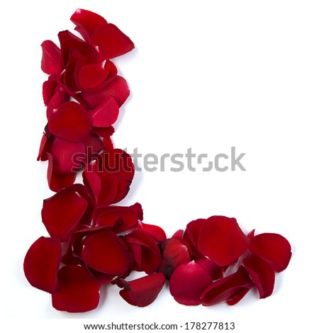 The letter L for love is written with rose petals. White background. - stock photo
