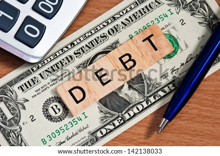 The letters DEBT on  dollar banknote business concept - stock photo