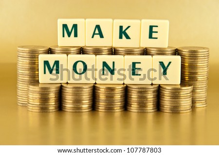 the letters MAKE MONEY with stacks of coins on gold background - stock photo