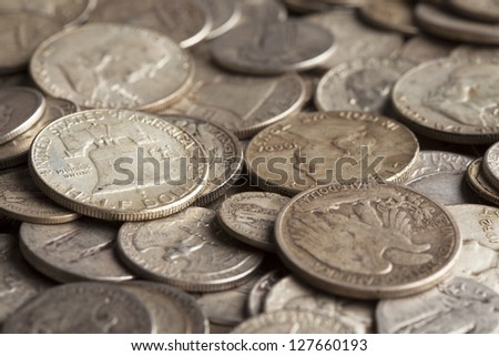 The Liberty Bell is shown on a coin pile with many other silver coins. - stock photo