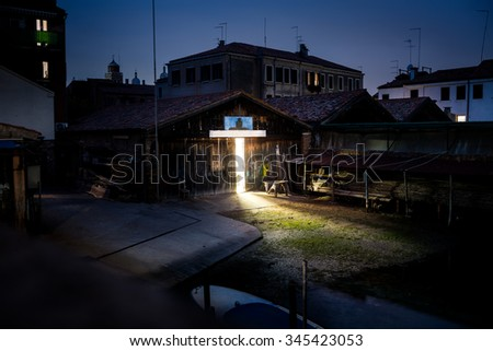 The light coming from old warehouse or workshop in the night. Mysterious view of the dark house in the night in the historical city or town in Europe. - stock photo