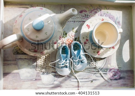 The light from the window on the kettle cup of baby shoes booties newborn baby boy - stock photo